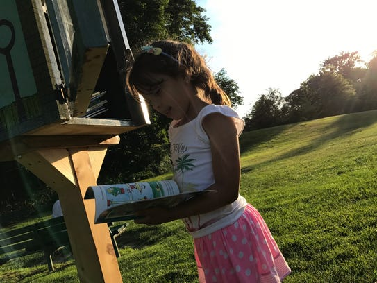 """Isabella Diaz, 7, inspects a """"Little Free Library"""""""