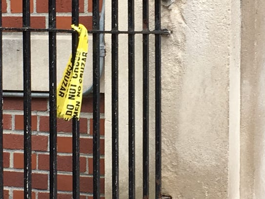 Police tape tied to a railing at the entrance to an