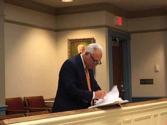 Attorney William Laufer examines documents during a