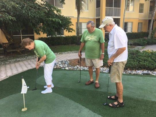 Residents take part in a putting contest as part of