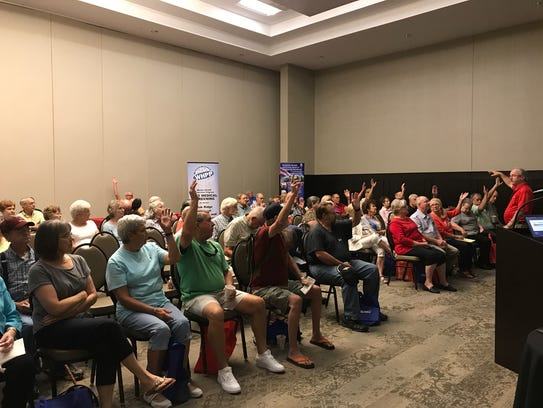 Former K-25 site workers raise their hands at a town