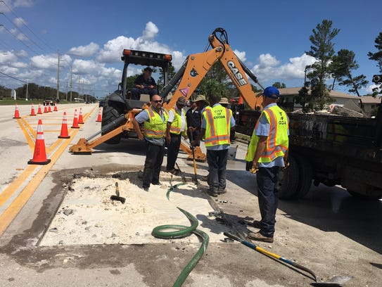 Cocoa workers fix a water line break Tuesday near Eastern