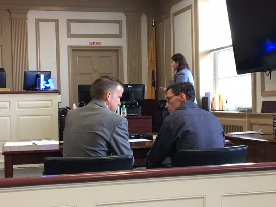 From left, defense lawyer Scott Wilhelm confers with
