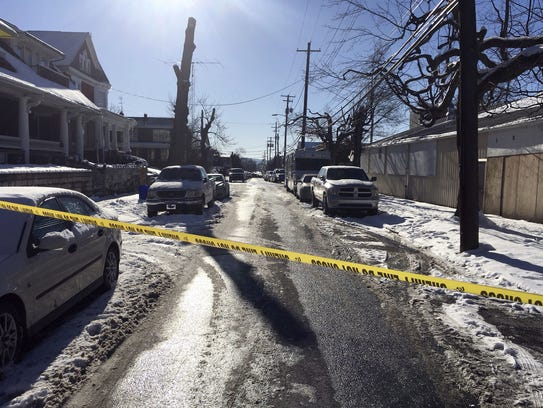Crime tape stretches across a road near the scene of