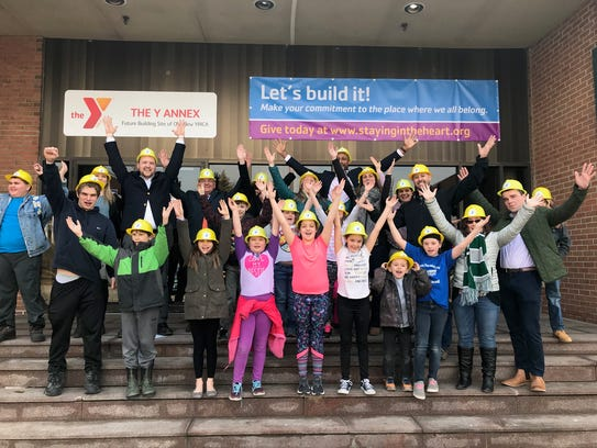 YMCA kids and staff pose outside the new location for