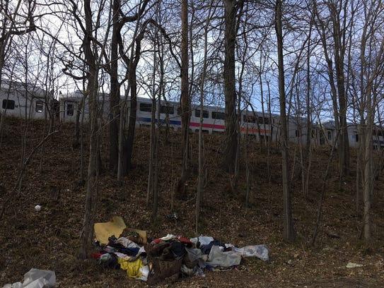 NJ Transit train passes by the tent city near the Dunellen-Piscataway