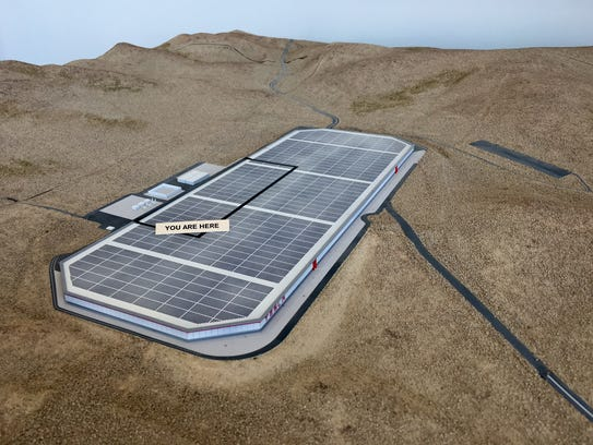 A model at the Gigafactory shows, outlined in black,