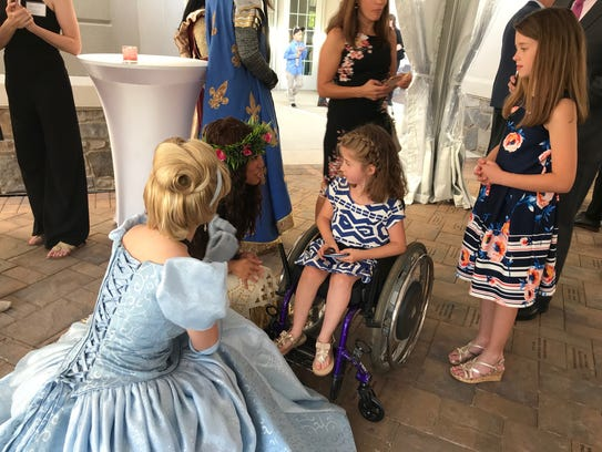 Klara Pederson, 8, of Mantua chats with Moana and Cinderella