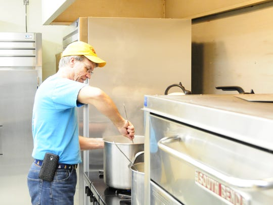 Volunteer Jeremy Thompson stirs a pot during a prep