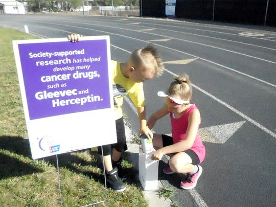 Tre Pennington, 5, and Aaliyah Pennington, 7, set up luminarias along the track Saturday in preparation for the Relay for Life at Navajo Preparatory School in Farmington.