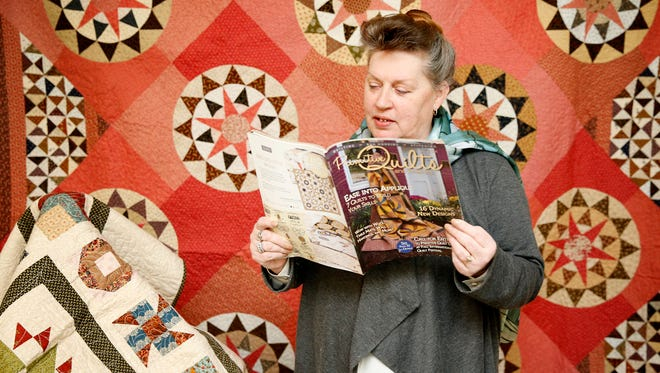 """Cathleen Koons-Wiggs' """"Millstone"""" quilt is featured on the cover of Primitive Magazine Spring 2016 issue. She has quilted for close to 20 years, and has completed more than 150 quilts."""