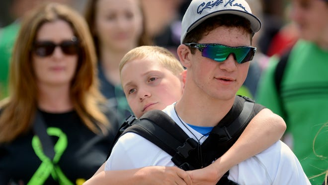 Hunter Gandee carries his brother Braden up Hagadorn Road near the campus of MSU on his way to the Capitol on a 111-mile walk to raise awareness for cerebral palsy.