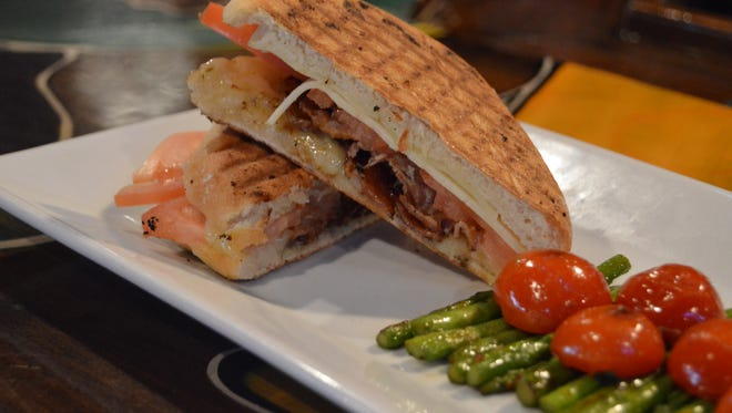 Roadie Joe's cuban panini features house braised pulled pork, freshly sliced ham, provolone, spicy pickles and is finished with a house made grainy mustard aioli.