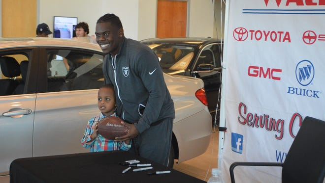 After signing an autograph, Oakland Raiders running back Jalen Richard poses with a young fan Jan. 24 at Walker BMW.