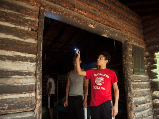 15-year-old Jaydakus Medina of Pennsauken, a member of the Lifting Up Camden's Youth program, uses a flashlight to get a better look at a spider he found in his sleeping quarters shortly after arriving to the Pine Hill Scout Reservation, where he and other members of the Lifting Up Camden's Youth program will be camping over the weekend.   01.01.14