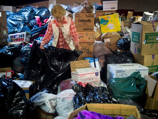 Volunteer Carolyn Blazier sorts through donated items at a warehouse in Sevierville on Dec. 5, 2016.