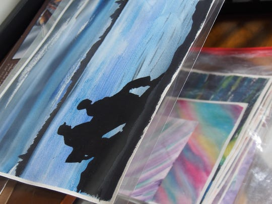 Stacks of watercolor backgrounds stand awaiting further inspiration. On the shelf above, a pair of shadowed figures look over a body of water.