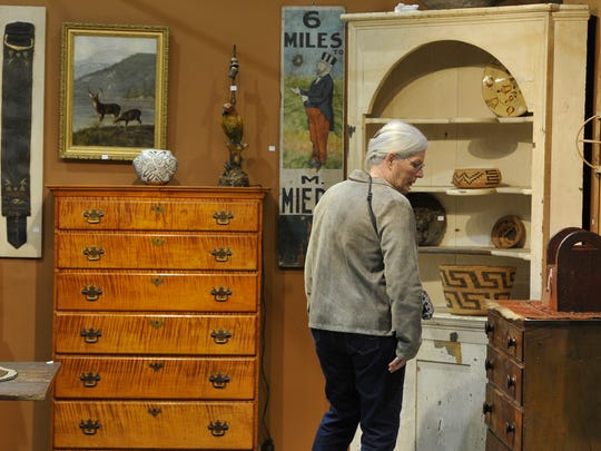 Sue Wollard from Chester County, Pennsylvania checks out the antique furniture for sale at the Greater York Antiques Show at Utz Arena of the York Expo Center on Nov. 13. Prices for antiques have fallen since the early 2000s, presenting a buying opportunity for collectors, experts said.