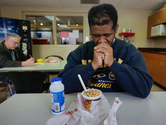 James Robertson, 56, of Detroit, prays before eating