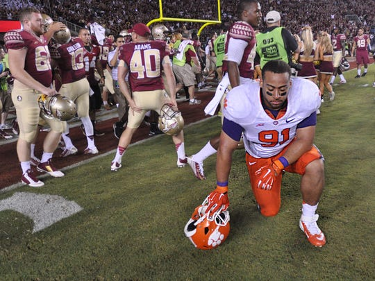 Clemson defensive tackle Josh Watson kneels while Florida State celebrates after a 23-17 overtime loss at Doak Campbell Stadium on Sept. 20, 2014.