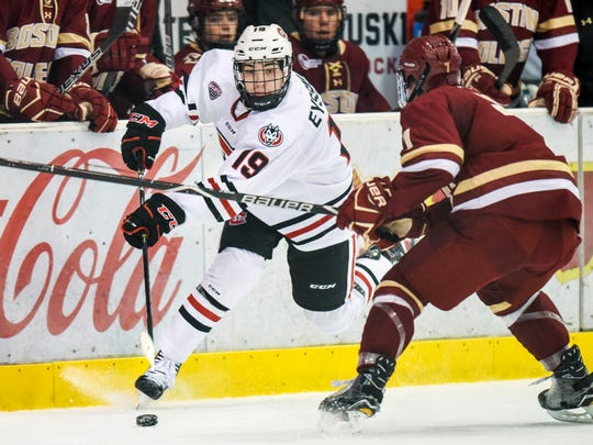 St. Cloud State's Mikey Eyssimont passes the puck around Boston College's Connor Moore during the first period  Friday, Oct. 20, at the Herb Brooks National Hockey Center.