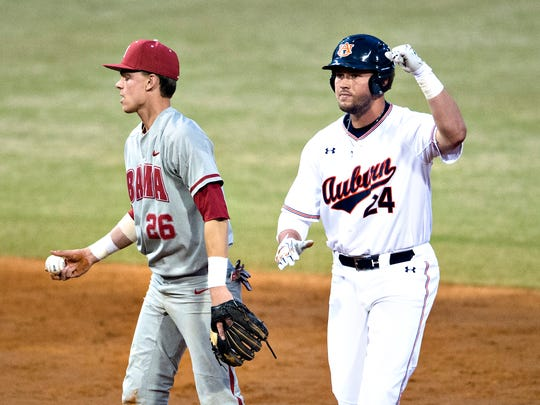 Auburn player Conor Davis celebrates after hitting a double as Alabama infielder Jett Manning (26) walks away during the Capitol City Classic between Alabama and Auburn on Tuesday, March 27, 2018, in Montgomery, Ala.