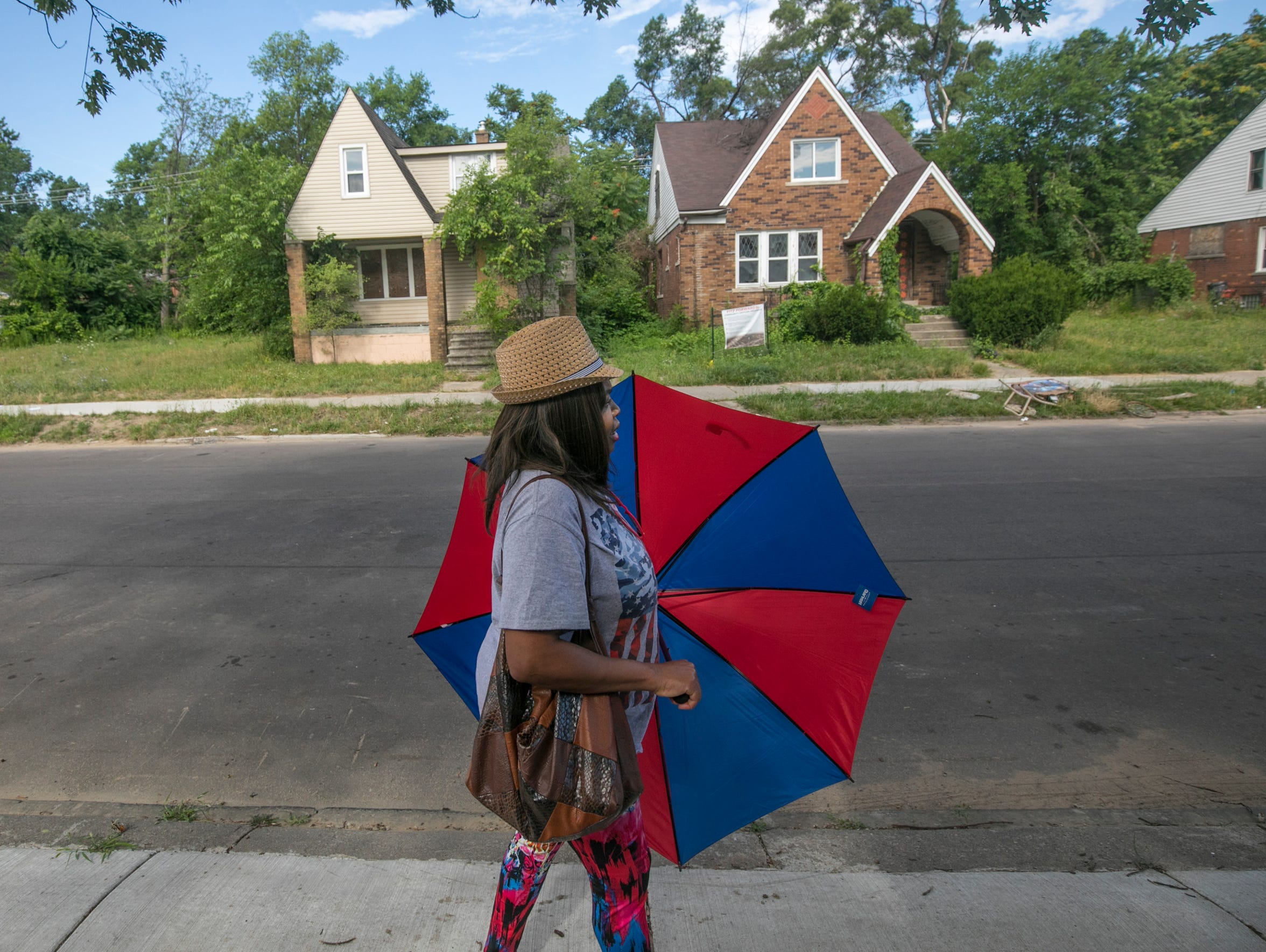 Renee Jones, 49, of Woodingham Drive said she would be more inclined to stay in the neighborhood if some of the abandoned homes are renovated. On Thursday, she walks by two homes slated for the Fitzgerald neighborhood revitalization project.