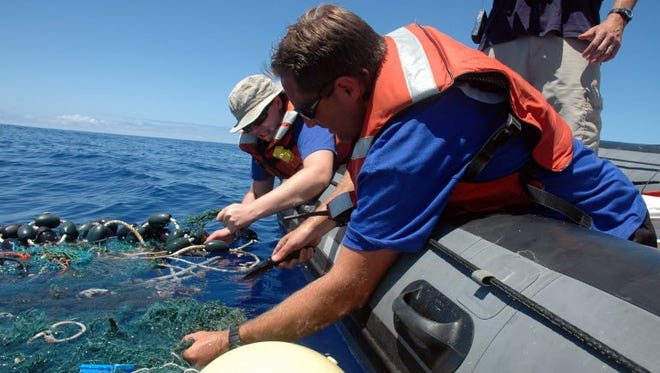 In this Aug. 11, 2009 file photo provided by the Scripps Institution of Oceanography shows Matt Durham, center, pulling in a large patch of sea garbage with the help of Miriam Goldstein, right, in the Pacific Ocean. Plastics discarded by people often end up in the ocean, creating coastal pollution that harms marine life and gathers out at sea in what's become known as the great Pacific garbage patch.
