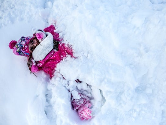 Becca, 7, lays burring in the snow at her home in Newark,