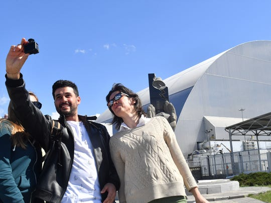 Tourists take pictures at Chernobyl's New 355 foot