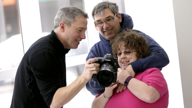 Photographer Rick Guidotti shows Robert and Jennifer Kuhr of Menasha their portrait Wednesday during a photo shoot with SOAR Fox Cities at the Trout Museum of Art in downtown Appleton.