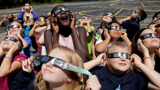Fourth-graders at Clardy Elementary School in Kansas City, Mo., practice the proper use of their eclipse glasses on Aug. 18, 2017.