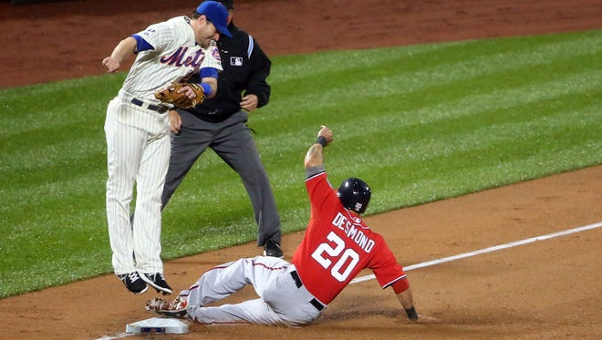 Washington Nationals shortstop Ian Desmond steals third as New York Mets third baseman Daniel Murphy is late to tag during the fourth inning at Citi Field.