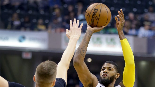 Indiana Pacers forward Paul George (13) shoots a three-pointer over New York Knicks forward Kristaps Porzingis (6) in the first half of their game Monday, January 23, 2017, evening at Bankers Life Fieldhouse. The Pacers lost to the Knicks 109-103.