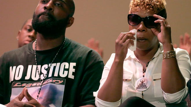 A Wilmington funeral home plans to send a book of condolences from local residents to the family of Michael Brown Jr., the teenager killed in Ferguson, Missouri. His parents, Michael Brown Sr. and Lesley McSpadden, listen to a speaker during a rally last week.