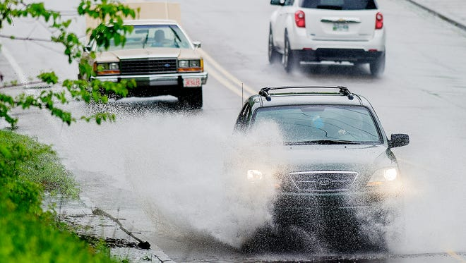 Vehicles drive through a large puddle of water along Central Avenue and Coram Street during an afternoon rainfall in Knoxville, Tennessee on Tuesday, April 18, 2017.