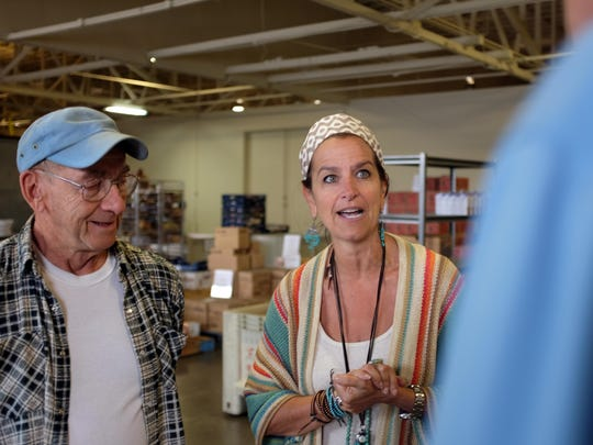 Executive Director Melissa Kendrick of the Food Bank for Monterey County speaks with Mel Dern, left, and Bob Nelson, right, from St. Vincent de Paul-Madonna Del Sasso Church.