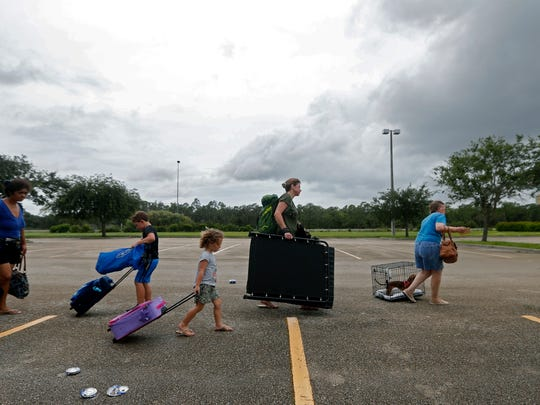 Evacuees stand in line to enter the Germain Arena, which is being used as a fallout shelter, in advance of Hurricane Irma, in Estero, Fla., Saturday, Sept. 9, 2017.