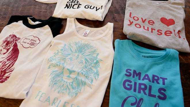 """Gender-neutral clothing made by Courtney Hartman is displayed at her home in Seattle. Hartman owns Jessy & Jack, a collection of unisex T-shirts, and Free to Be Kids, where a shirt with the slogan, """"I'm a Cat Guy"""" comes in blue, gray and yellow."""