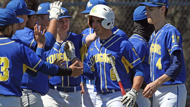 Nicholas Conte, holding the bat, celebrates with his teammates after hitting a home run for North Providence in a game last April against Scituate.