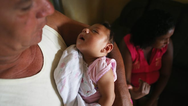 Joao Batista Bezerra holds his 3-month-old daughter, Alice Vitoria Gomes Bezerra, who has microcephaly, in Recife, Brazil, as her mother, Nadja Cristina Gomes Bezerra, sits nearby.