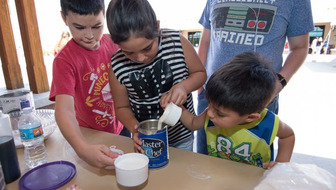 Jacob Salazar, 5, is assisted by his sister Kaylee Ann Malinowski and cousin Christian Regur as he gets his can ready to make ice cream at the 2016 Ice Cream Sunday event held at the New Mexico Farm & Ranch Heritage Museum.
