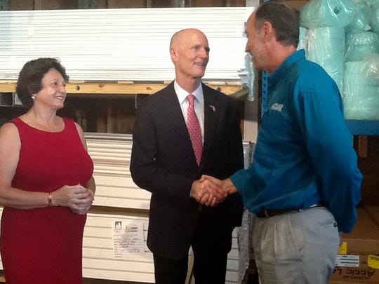 Rep. Kathleen Passidomo, R-Naples looks on as Gov. Rick Scott shakes hands with David Weston, chief operating officer of Naples Lumber and Supply, at a jobs announcement on Friday, July 15, 2016.