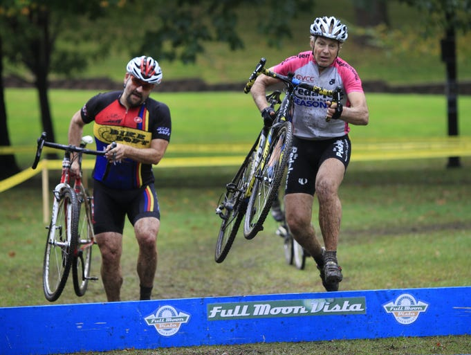Competitors jump the barriers in the masters mens cyclocross race at Cobbs Hill.