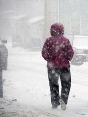 A pedestrian walks down the street during asnowstorm