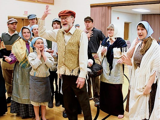 "Avram, the bookseller played by Dennis Cravens, delivers the final and wildly inaccurate version of the rumor to the shocked villagers of Anatevka during the musical number ""The Rumor."""