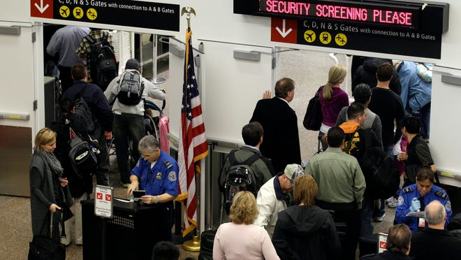 FILE - TSA agents check passenger identification at a security gate, Friday, Nov. 19, 2010, at Seattle-Tacoma International Airport in Seattle. (AP Photo/Ted S. Warren)