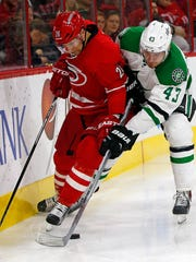 Carolina Hurricanes' John-Michael Liles (26) and Dallas Stars' Valeri Nichushkin (43) vie for the puck during the second period of an NHL hockey game Friday, Nov. 6, 2015, in Raleigh, N.C. (AP Photo/Karl B DeBlaker)