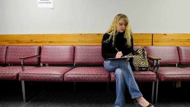 Becky Harte fills out paperwork in the waiting area outside her doctor's office at the MSU Clinical Center on Monday, Oct. 26, 2015. Harte, an employee of the Department of Health & Human Services, is suing the state, alleging she was discriminated against because she has multiple sclerosis.
