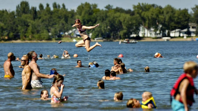 People swim at Lakeside Park in Big Lake. As crowds gather outdoors to enjoy summer, consider common courtesies with your sound devices.